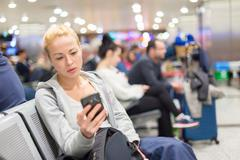 Female traveler using cell phone while waiting. Stock Photos