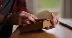 4K Close up on hands of unrecognizable man flicking through the pages of a book - stock footage