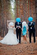 Groom, bride and witnesses walking in autumn pine forest Stock Photos