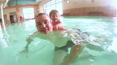 Toddler girl swimming with her father at indoor swimming pool. Stock Footage