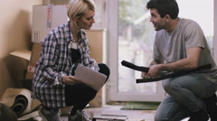 Couple putting together flatpack shelving - stock footage