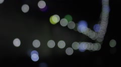 Colored lights generated by cars passing on the road at night bokeh Stock Footage