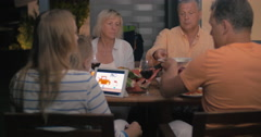 Friendly family having late outdoor dinner Stock Footage