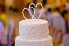 Multi-tiered white wedding cake with two hearts above Stock Photos