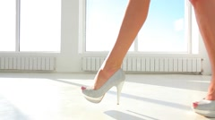 Girl in high heel shoes walking against panoramic sunny window. Dolly shot Stock Footage