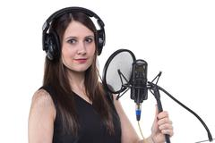 Smiling woman in headphones with microphone - stock photo