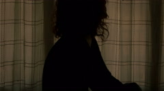 Sad and pensive woman in a dark room Stock Footage