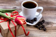 Single cut tulip on gift box with coffee and chocolate on stressed wood - stock photo