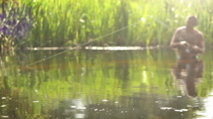 A fisher standing waist-deep in the water trying to catch a fish Stock Footage