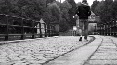 Black and white: man walks along the medieval dam in Liberec (Czech Republic) - stock footage