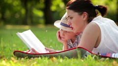 Mother and son spend their time reading on a summer afternoon in the park Stock Footage