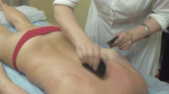 Masseuse make remedial stone therapy massage of back to to slim woman in saloon - stock footage