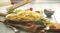 A cook grates the cheese upon the plate of Italian pasta Stock Footage