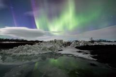 Northern Lights above an iceberg in a lagoon Stock Photos