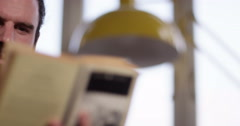 4K Close up portrait of man relaxing, completely engrossed in a book Stock Footage