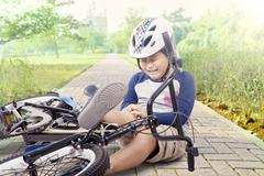 Boy hurt after falling off his bicycle Stock Photos