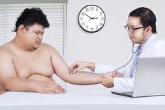 Doctor checking the patient heartbeat - stock photo