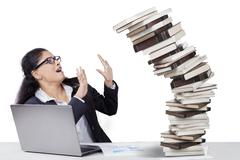Frustrated Indian worker with falling books Stock Photos