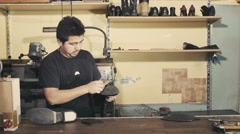 Shoemaker brushinng sole of a apair of boots Stock Footage