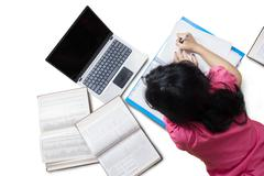 Student studying with laptop in studio - stock photo