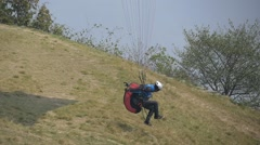 Paraglider flying over the take off at low altitude Stock Footage