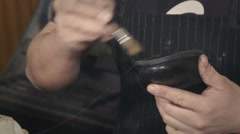 shoemaker repairing the sole of a leather boot - stock footage