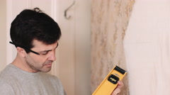 Adult Man with spirit level measuring wall in new home - stock footage