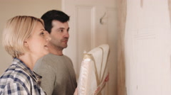 Adult couple fitting painting on the wall - stock footage