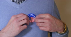 Voter Places I Voted Sticker on Sweater Stock Footage