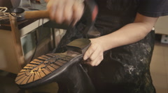 Shoemaker fixs a sole with a hammer Stock Footage