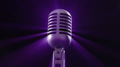 Generic retro style metallic microphone reflecting purple stage lighting as it r - stock footage