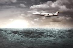 Private jet flying over the ocean Stock Photos