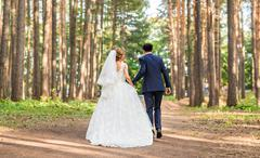 Bride and groom walking away in summer park outdoors Stock Photos