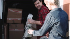 Adult Couple moving into new house with homeware - stock footage