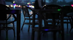 Empty tables in the bar on the waterfront with people passing in the background - stock footage