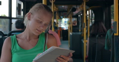 Young woman entertaining with pad during bus ride Stock Footage