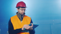 Builder works with the tablet, blurred blue background Stock Footage
