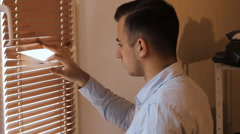 Young businessman peeping through the window blinds Stock Footage