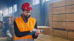 Warehouse worker uses a tablet. Writes data on the availability of building Stock Footage