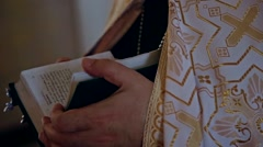 The priest turns the pages of the Bible Stock Footage