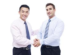 Asian and caucasian businessmen shaking hands Stock Photos