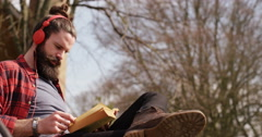 4k, Young man listening to music and  deeply engrossed in reading a book Stock Footage