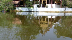 Reflection from The Wihan at Wat Phrao, Tak in the water Stock Footage