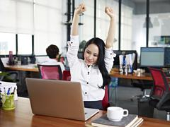 Asian business woman stretching arms in office Stock Photos