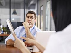 skeptical interviewer looking at interviewee - stock photo