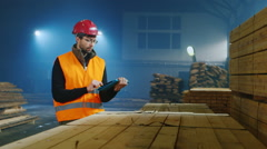 Warehouse worker is working on logistics, uses tablet - stock footage