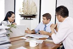 multinational businesspeople discussing sales performance in office - stock photo