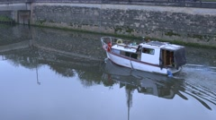 Motorboat chugging up the canal in the city of Bath Stock Footage