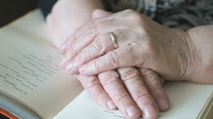 Old woman reading a book of poems Stock Footage