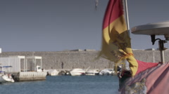 Fuengirola port with tattered Spanish flag - stock footage